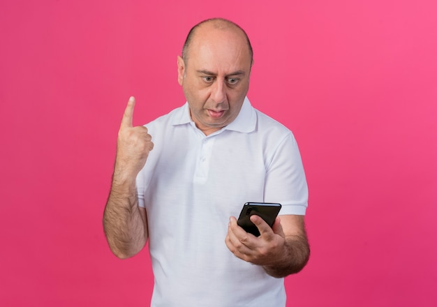 Pod wrażeniem przypadkowy dojrzały biznesmen trzymając telefon komórkowy i podnosząc palec na białym tle na różowym tle z miejsca na kopię i patrząc na niego