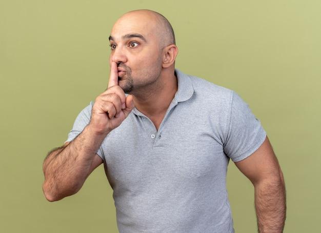 Pod wrażeniem przypadkowy mężczyzna w średnim wieku, patrzący na bok, wykonujący gest ciszy odizolowany na oliwkowozielonej ścianie