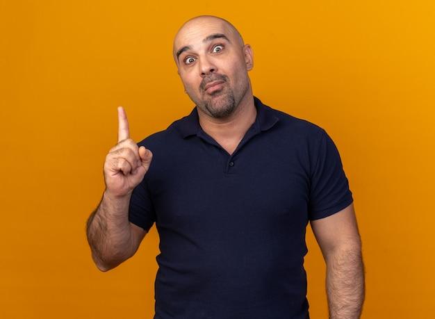 Pod wrażeniem przypadkowy mężczyzna w średnim wieku, wskazujący w górę, odizolowany na pomarańczowej ścianie