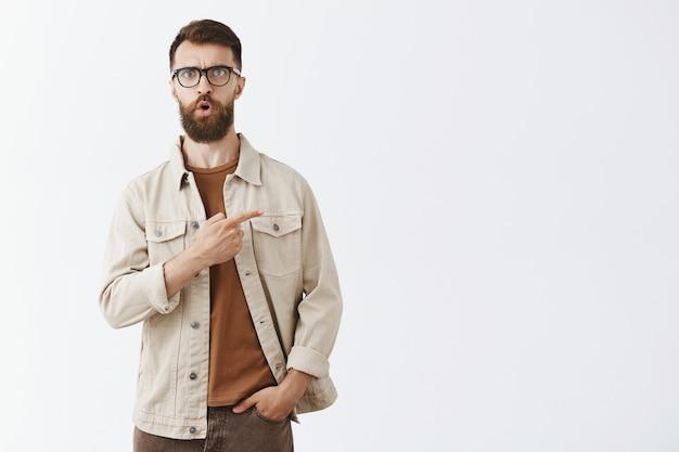 Pod wrażeniem przystojny brodaty mężczyzna w okularach pozuje przy białej ścianie