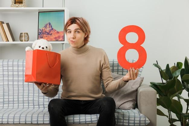 Pod wrażeniem przystojny facet w szczęśliwy dzień kobiet trzymający numer osiem z torbą na prezenty siedzący na kanapie w salonie