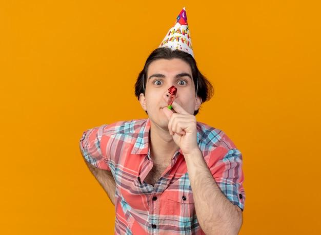 Pod wrażeniem przystojny kaukaski mężczyzna noszący czapkę urodzinową dmuchający gwizdek na imprezę