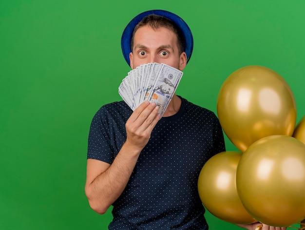 Pod wrażeniem przystojny kaukaski mężczyzna ubrany w niebieski kapelusz partii trzyma balony z helem i pieniądze na białym tle na zielonym tle z miejsca na kopię