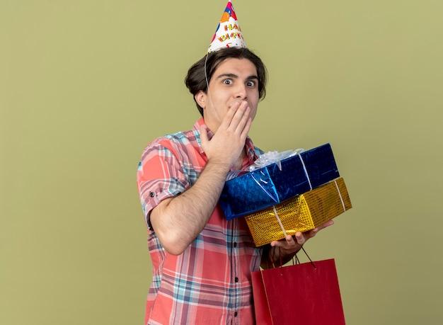 Pod wrażeniem przystojny kaukaski mężczyzna w czapce urodzinowej trzyma pudełka na prezenty i papierową torbę na zakupy shopping