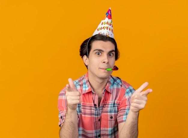 Pod wrażeniem przystojny mężczyzna rasy kaukaskiej w czapce urodzinowej dmuchający gwizdek wskazujący na aparat dwiema rękami