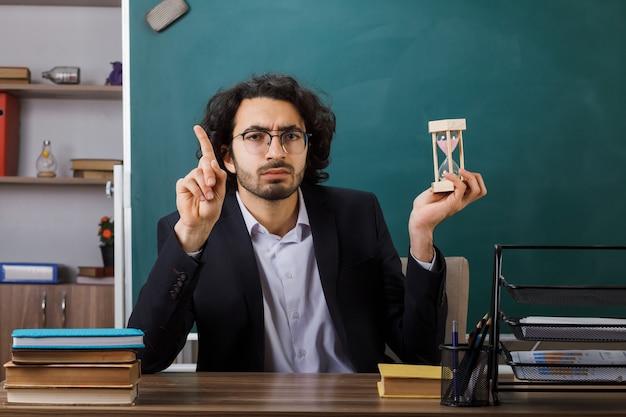 Pod wrażeniem punktów na nauczyciela w okularach trzymającego klepsydrę, siedzącego przy stole ze szkolnymi narzędziami w klasie
