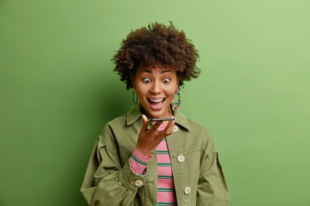Pod wrażeniem szczęśliwa, zaskoczona kobieta czuje się podekscytowana, wpatrując się w wyświetlacz smartfona, trzymając komórkę blisko ust, wysyła wiadomość głosową ubrana w modne ubrania odizolowane na zielonej ścianie studia