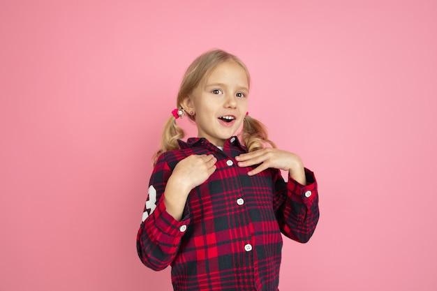 Pod wrażeniem, uroczy. kaukaski portret małej dziewczynki na różowej ścianie. piękna modelka z blond włosami.