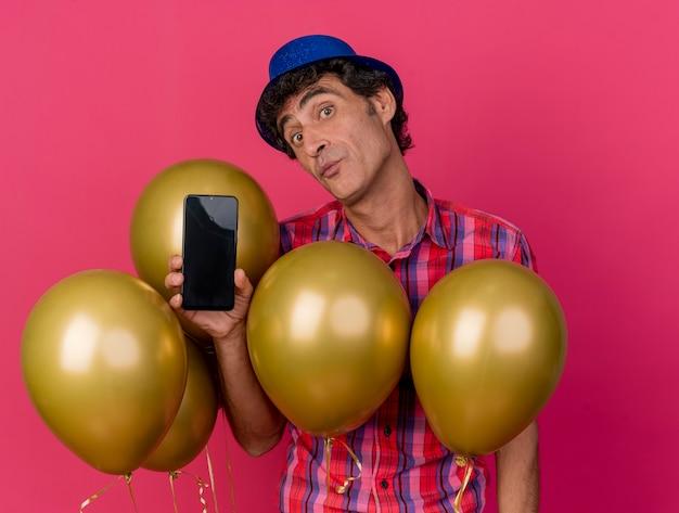 Pod wrażeniem w średnim wieku kaukaski mężczyzna party kapeluszem stojącym za balonami pokazujący telefon komórkowy patrząc na kamery na białym tle na szkarłatnym tle
