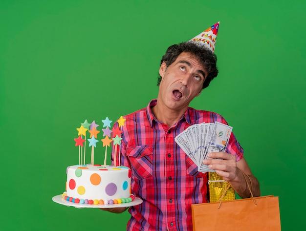 Pod wrażeniem w średnim wieku kaukaski mężczyzna w czapce urodzinowej, trzymając tort urodzinowy worek papierowy prezent i pieniądze patrząc w górę na białym tle na zielonym tle