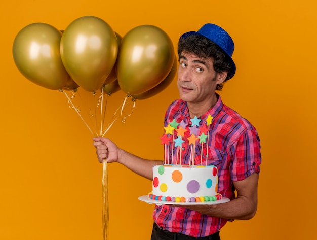 Pod wrażeniem w średnim wieku kaukaski mężczyzna w kapeluszu imprezowym stojący w widoku profilu, trzymając balony i tort urodzinowy, patrząc z boku na białym tle na pomarańczowym tle