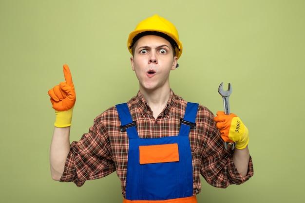 Pod wrażeniem wskazuje na młodego budowniczego mężczyznę noszącego mundur w rękawiczkach trzymających klucz płaski