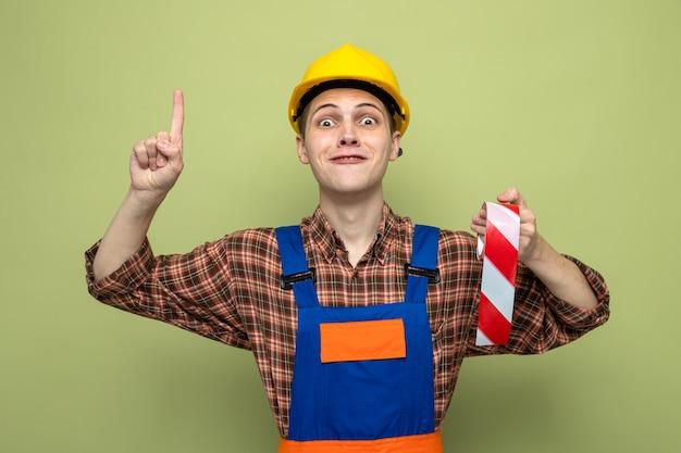 Pod wrażeniem wskazuje na młodego budowniczego płci męskiej noszącego mundur trzymający taśmę klejącą