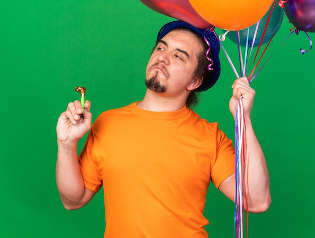 Pod wrażeniem wyglądającego boku młodego mężczyzny w kapeluszu imprezowym, trzymającego balony z gwizdkiem imprezowym odizolowanym na zielonej ścianie