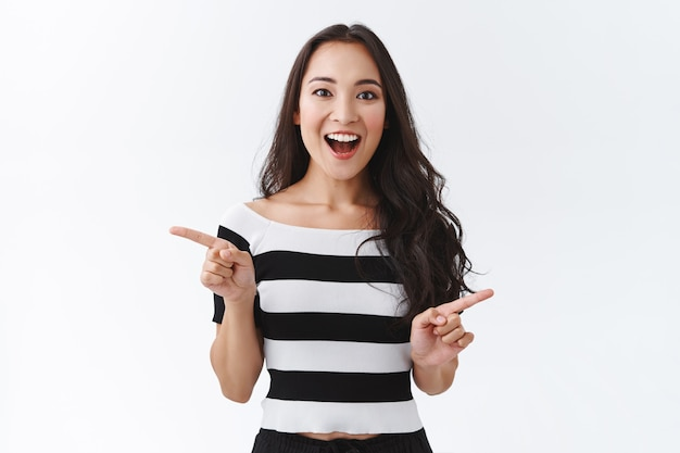 Pod wrażeniem, zafascynowana, przystojna dziewczyna z azji wschodniej w pasiastym t-shircie, wskazująca bokiem, pokazująca reklamy z lewej i prawej strony, uśmiechnięta, rozbawiona i zdumiona, z rozbawionym aparatem, białe tło