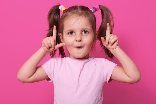Pod wrażeniem zaskoczone, emocjonalne dziecko podnosi palce do góry, otwiera zdziwione usta, uważnie podnosi wzrok. mały, zabawny model pozuje w jasnoróżowej koszulce w stylu jasnoróżowym, kolorowe falbany.