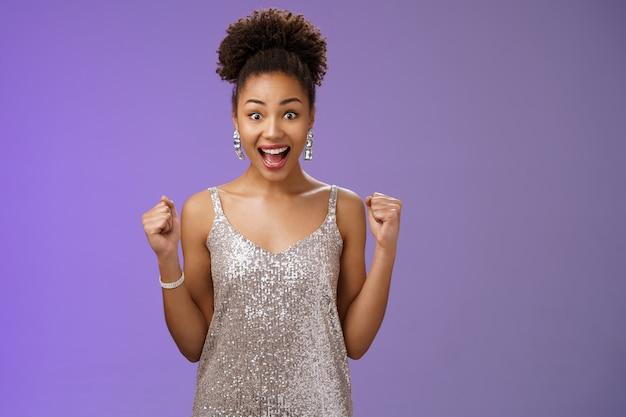 Pod wrażeniem zaskoczony zachwycony radosny czarujący elegancka afro-amerykańska kobieta wygrywająca pieniądze kasyno osiągająca sukces krzycząc radośnie podnosząc pięści zwycięstwa triumf gest dopingujący chętnie niebieskim tle.