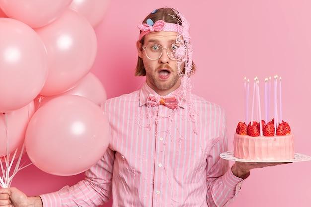 Pod wrażeniem, zszokowany młody mężczyzna w świątecznym ubraniu wpatruje się w wytrzeszczone oczy, trzyma usta otwarte, otrzymuje nieoczekiwane gratulacje od znajomego posmarowanego kremem, trzyma tort urodzinowy i nadmuchane balony