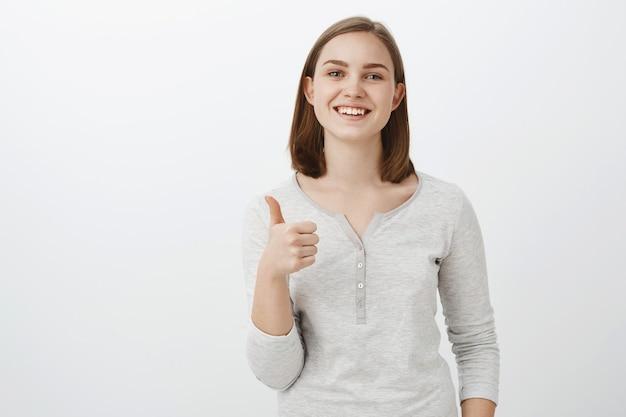 Podaję kciuki w górę. zadowolona, szczęśliwa, urocza młoda europejska kobieta o krótkich brązowych włosach, uśmiechnięta z wesołym wyrazem twarzy, lubiąca dobry wygląd przyjaciela podczas przymierzania nowych ubrań aprobujących na szarej ścianie