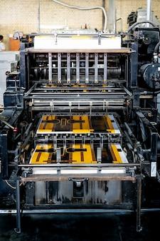Podajnik maszyny offsetowej przenosi papier metaliczny przez stół podający do fabryki zespołu drukującego