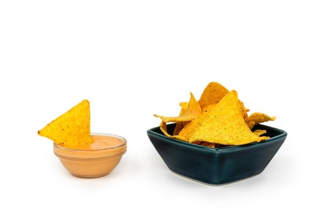 Podanie chrupiących nachos w talerzu z serem i sosem na białym talerzu.