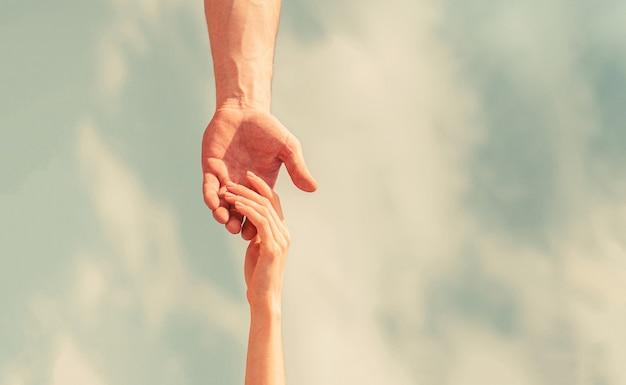 Podanie pomocnej dłoni. ręce mężczyzny i kobiety na tle błękitnego nieba. pionowy