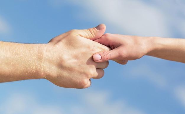 Podanie pomocnej dłoni. ręce mężczyzny i kobiety na tle błękitnego nieba. pomocna dłoń. ręce mężczyzny i kobiety sięgające do siebie, wsparcie. solidarność, współczucie i dobroczynność, ratunek.