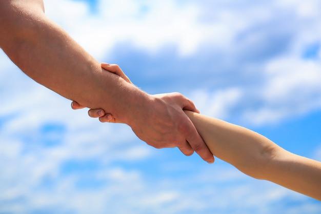 Podanie pomocnej dłoni. ręce mężczyzny i kobiety na tle błękitnego nieba. pomocna dłoń