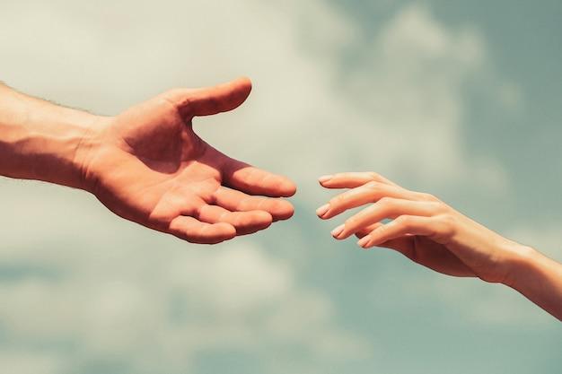 Podanie pomocnej dłoni. ręce mężczyzny i kobiety na tle błękitnego nieba