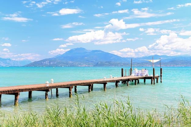 Podano stolik na wesele nad jeziorem. głęboka woda, góry i niebo. romantyczny dzień.