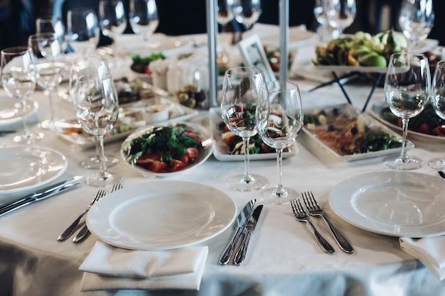 Podany stół z przekąskami i pustymi kieliszkami do wina.