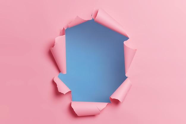 Podarte, zgrane różowe tło z otworem pośrodku na treść reklamową lub promocję.