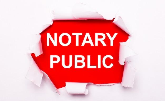 Podarty biały papier leży na czerwonym tle. na czerwono tekst jest biały notariusz publiczny