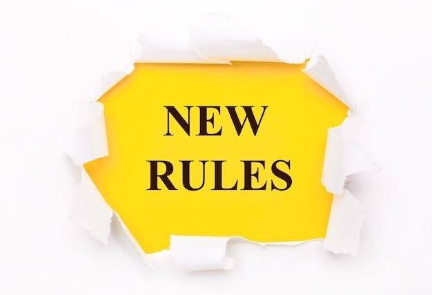 Podarty biały papier leży na jasnożółtej powierzchni z napisem nowe zasady