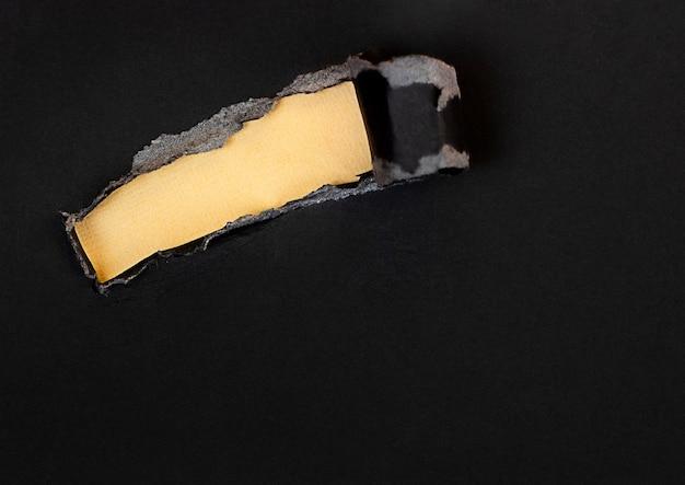 Podarty czarny papier na żółtym tle