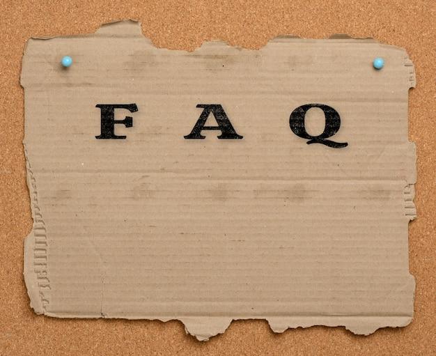 Podarty kawałek brązowego kartonowego papieru jest przypięty do tablicy korkowej. napis faq, wyszukiwanie odpowiedzi na pytania, pomoc w nawigacji