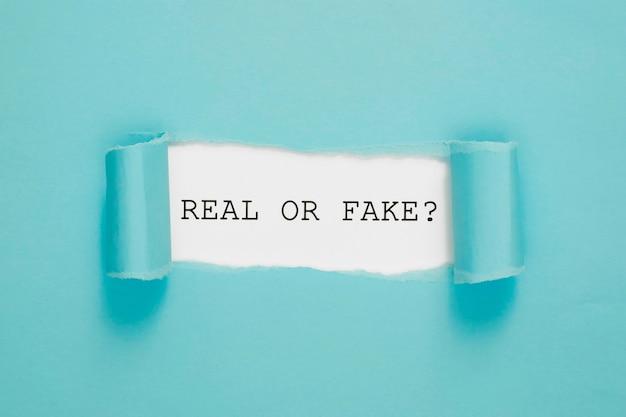 Podarty prawdziwy lub fałszywy papier na niebiesko-białej ścianie