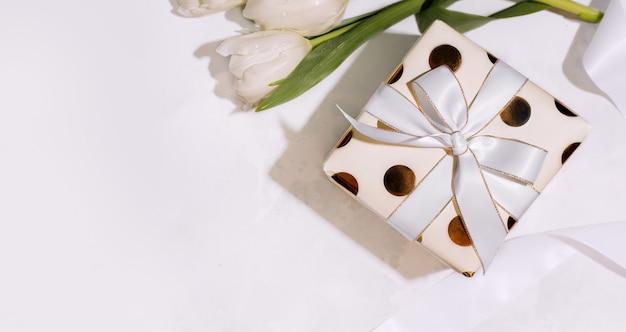 Podaruj białe kwiaty i cukierki w pudełku w kształcie serca na jasnoróżowym tle. widok z góry. skopiuj miejsce. transparent