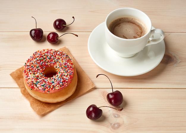 Podaruj sobie kawę i pączka z różową polewą, wysokokaloryczne śniadanie