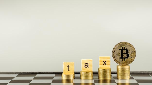 Podatek drewniany blok i bitcoiny na złotych monetach stosu. - koncepcja rachunkowości finansowej.