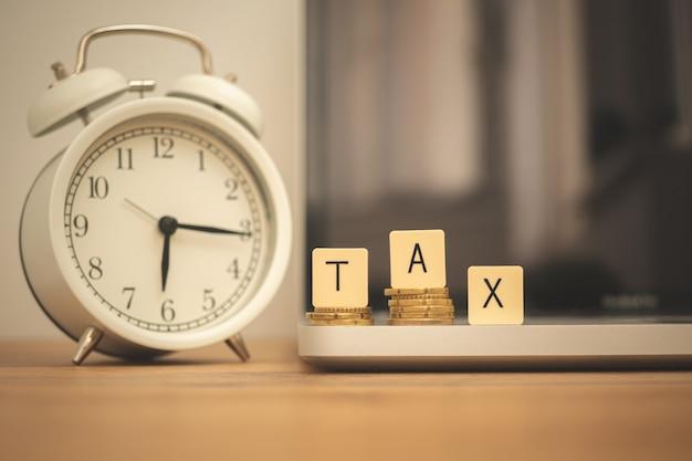 Podatek dzień tło. podatku słowo i budzik na biurku z laptopem. zarządzanie finansami i gospodarką, zdjęcie koncepcji obliczania budżetu