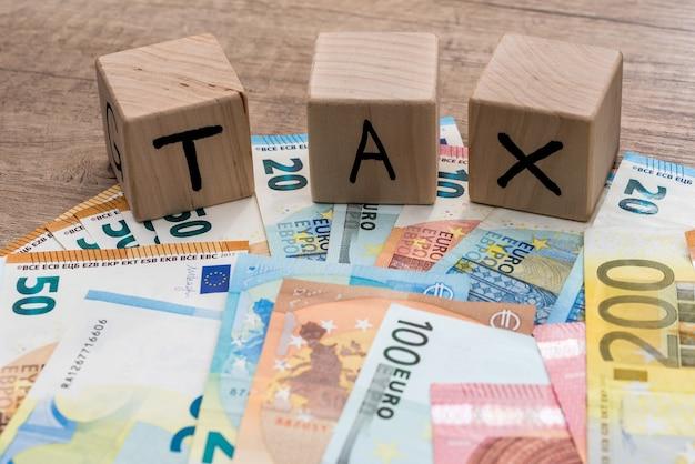 Podatek od drewnianych kostek na rachunkach euro jako tło