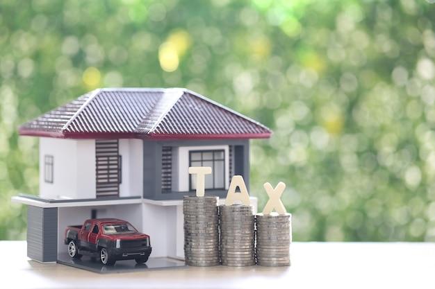 Podatek od nieruchomości, dom model ze stosem monet pieniądze i słowo podatku na zielonym tle, inwestycje biznesowe i koncepcja podatku od nieruchomości