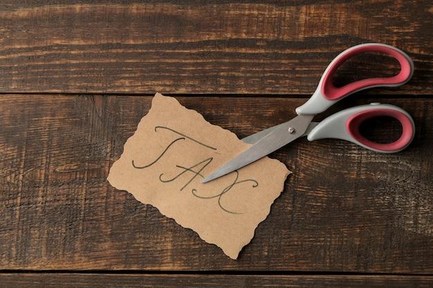 Podatek słowo z nożyczkami na brązowym tle drewnianych. widok z góry