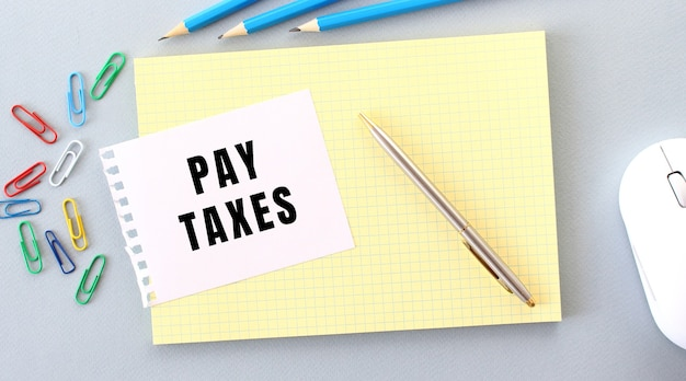 Podatki płatne jest zapisane na kartce papieru leżącej na notatniku obok materiałów biurowych. pomysł na biznes.