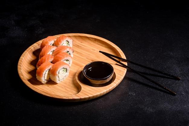 Podawane są różne rodzaje sushi. bułka z łososiem, awokado, ogórkiem. menu sushi. japońskie jedzenie.