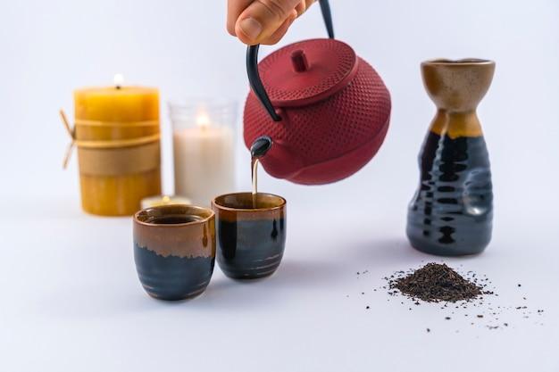 Podawanie japońskiej herbaty ze świecami oraz japońskiej filiżanki i szklanek