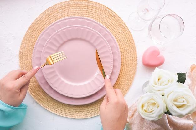 Podawany stół z pustymi talerzami, kobiece dłonie z nożem i widelcem, róże i szklanki.