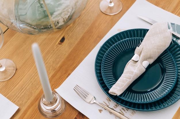 Podawany świąteczny stół z pustymi talerzami, sztućcami i serwetką z tkaniny.