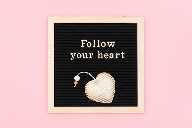 Podążaj za głosem serca. motywacyjny cytat złotymi literami i ozdobne serce z tkaniny na czarnej tablicy
